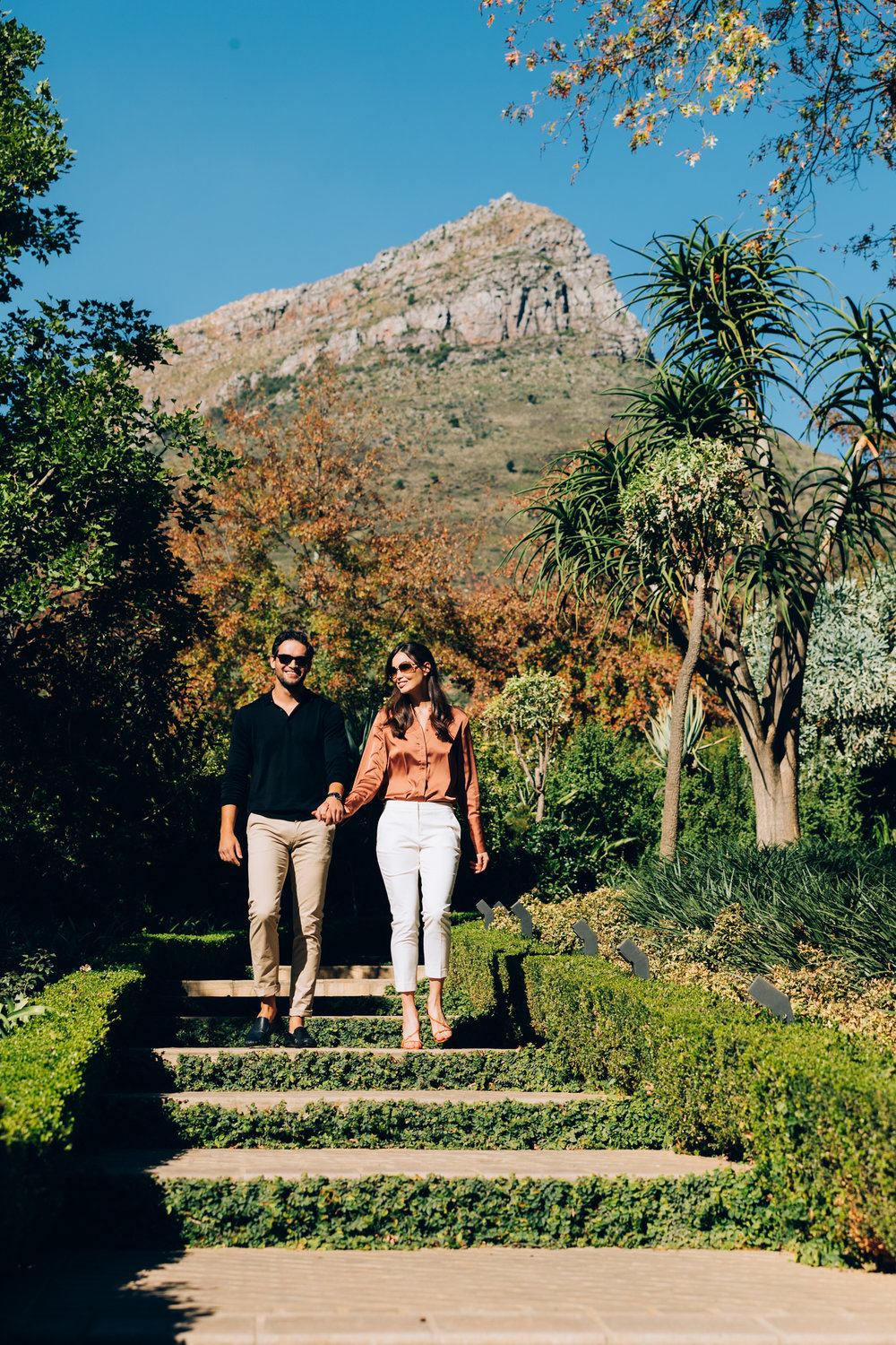 A couple walk down the stairs hand in hand toward the wine tasting room at Delaire Graff Estate with a view of the mountains behind them