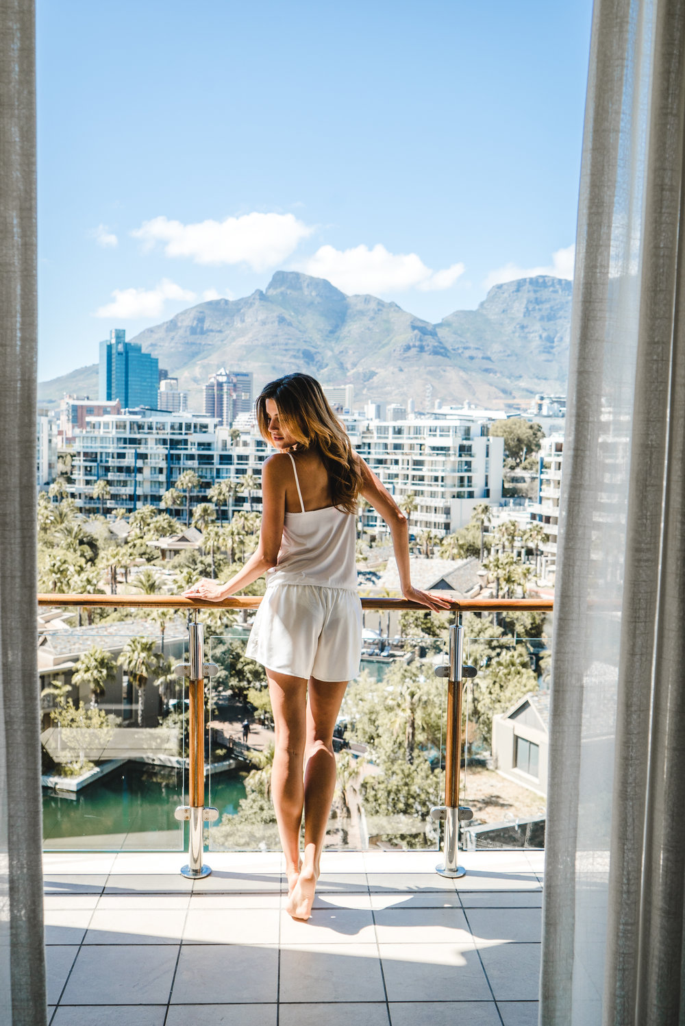 A girl standing on the balcony at One&Only Cape Town enjoying the view of Table Mountain in the morning