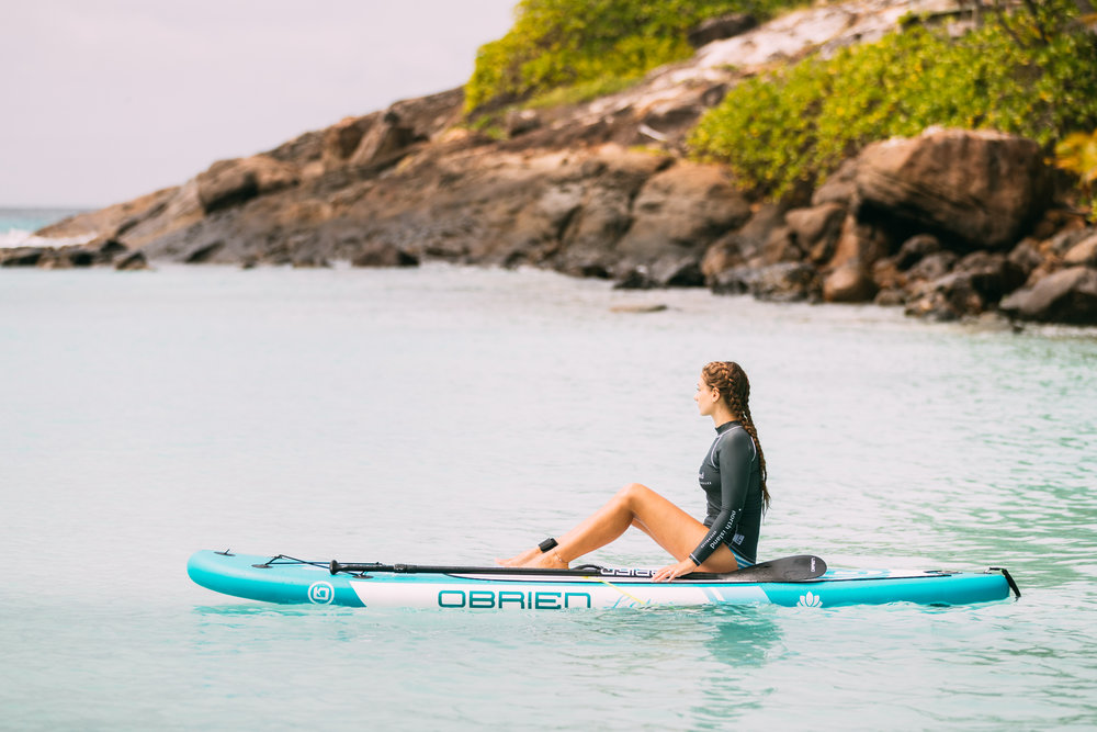 A girl sits on a stand-up paddleboard in the calm turquoise waters of North Island admiring the view