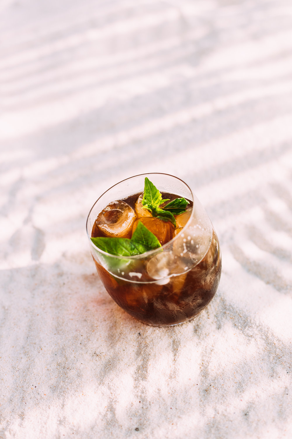 A refreshing Blackjack cocktail of bourbon, balsamic vinegar, basil and ginger beer shot on a white beach on North Island