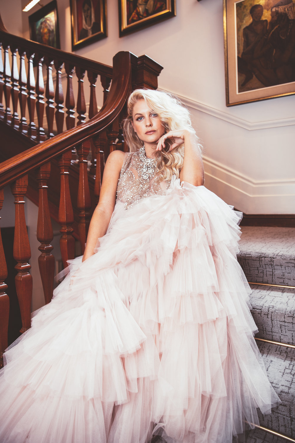 Girl sitting on staircase in pale pink Stefania Morland dress at Ellerman House