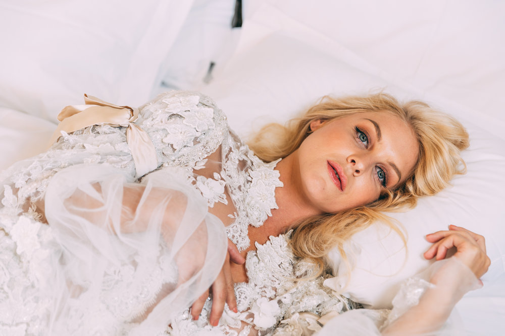 Girl lying in bed at Ellerman House dressed in white lace top by Stefania Morland