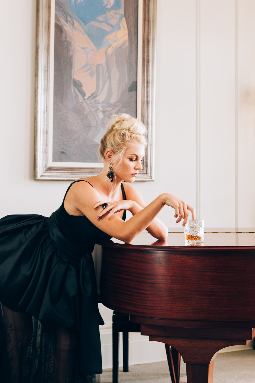 Girl drinking whiskey in black KluK CGDT dress at the piano at Ellerman House