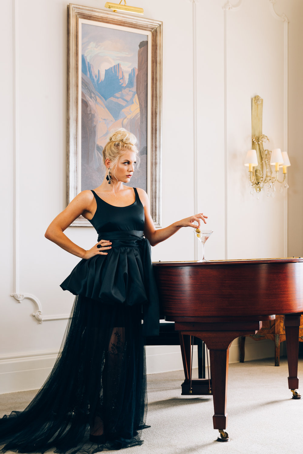 Girl standing at the piano drinking a martini in a black Kluk CGDT dress at Ellerman House