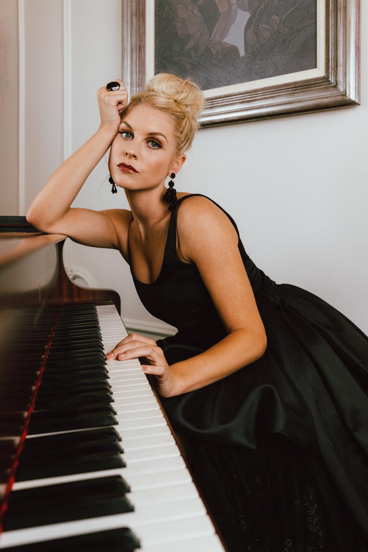 Girl leaning on piano in black KluK CGDT dress at Ellerman House