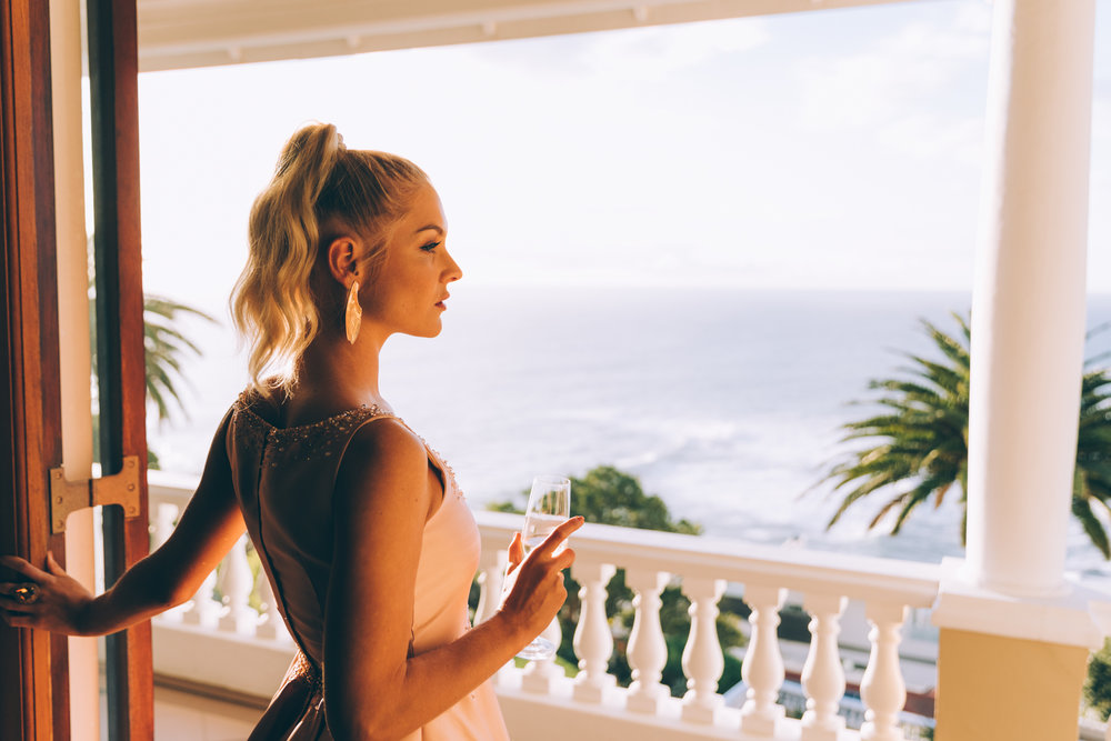 Girl drinking champagne in pale pink Gavin Rajah dress admiring the view at Ellerman House