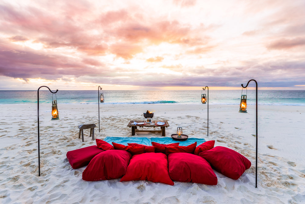 A romantic dinner set up on the beach with red cushions, turquoise picnic blanket, a bonfire and lanterns with Indian Ocean views at sunset