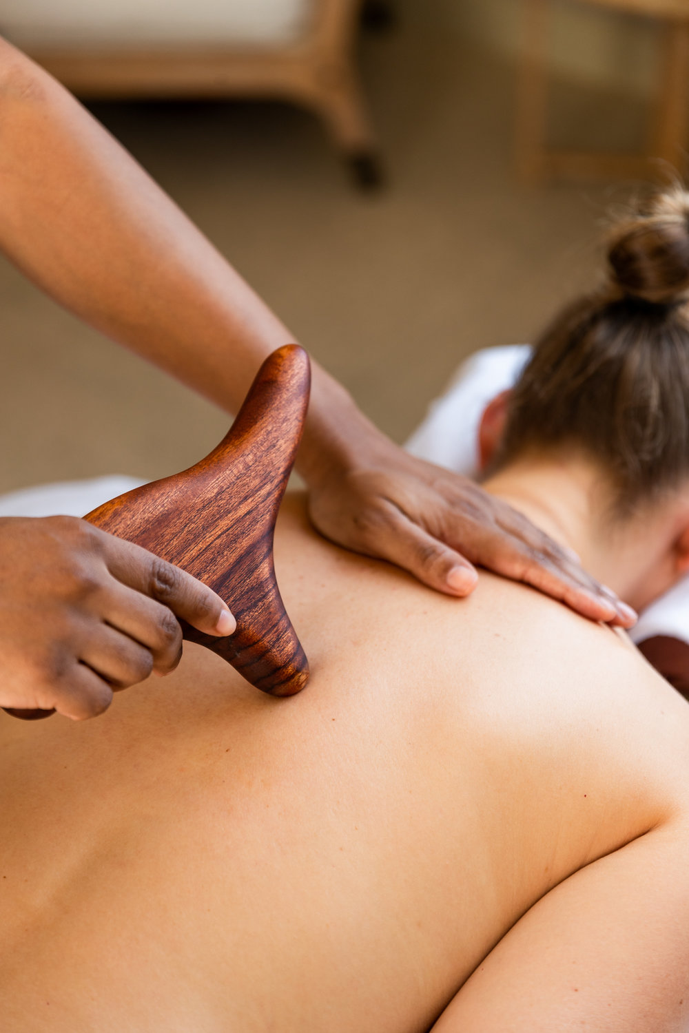 Female having a massage using wooden massage sticks at Delaire Graff Spa