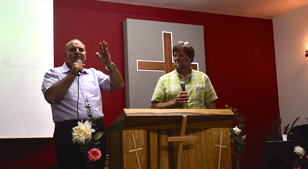 Terry O'Casey (on right), Professor of Christian Ministry and Biblical Studies at Northwest Christian University (Eugene, Oregon) shares a weekend message with the local church in Turan, Israel. Saleem Hanna (on left), minister, translates into Arabic. Photo by Bible Land Explorer Mike Taylor.