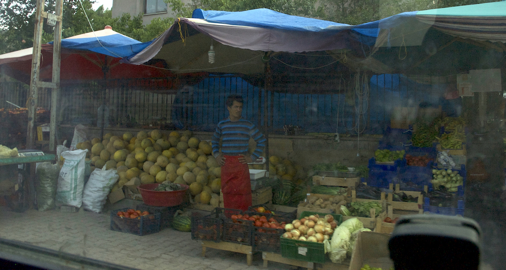 View to a fruit stand through the smudged glass of our vehicle.