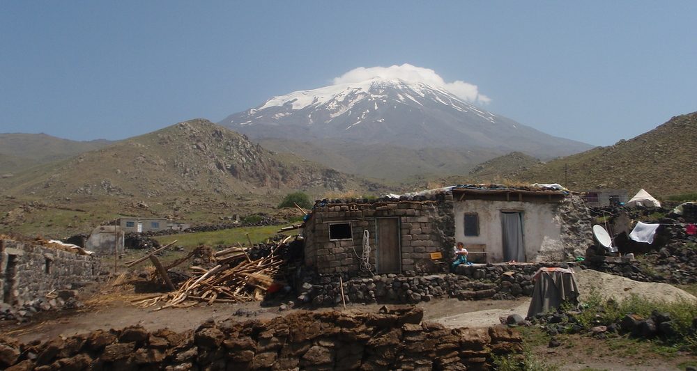 A house in Çevirme. The snowy peak of Agri Dagi, traditional Mt Ararat, rises in the distance. Dung-cakes are arranged on a wall in the foreground.
