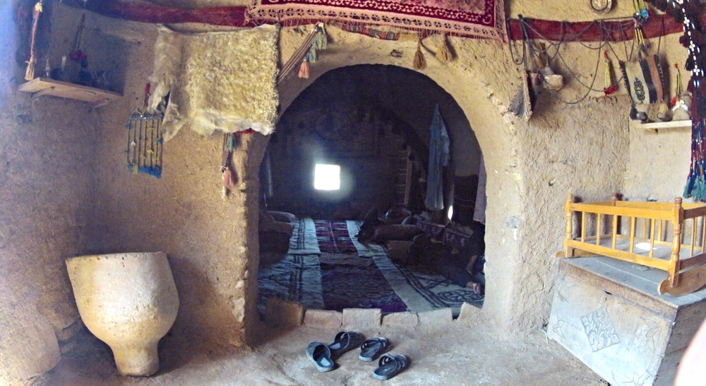 A passage between rooms. Men are sleeping on the floor just beyond. The walls are thick, creamy, and colorfully decorated. It is surprisingly clean inside this house of earth!