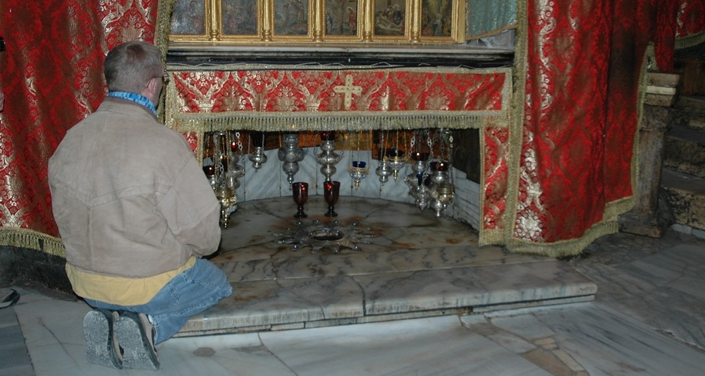 Kneeling before the altar that marks the traditional place where Jesus was born. This altar is located in a cave beneath the Church of the Nativity in Bethlehem.