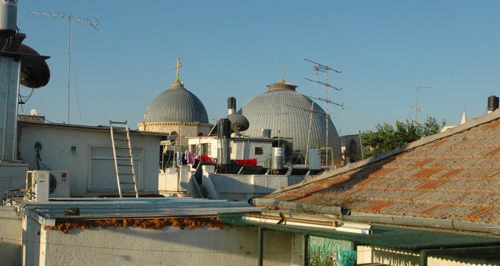 View from my roof to the twin domes of the Church of the Holy Sepulcher. It rises from the midst of despoiled humanity.