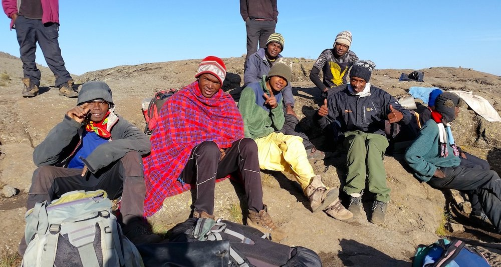 Our porters warm themselves in the sun. My man Dennis is there in the green coat and yellow pants.