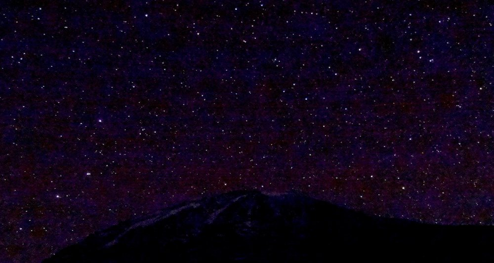 The night sky made the mountain look small.