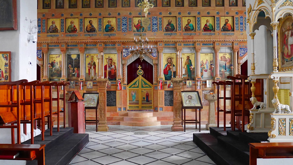 """The iconostasis is decorated with icons in an Orthodox church. It screens the sanctuary from the nave. Only a priest may pass through the """"Beautiful Gate"""" in the center. The iconostasis at Mar Nicola is considered a mason's masterpiece, cut from local stone."""