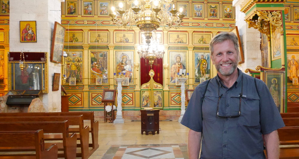 Yours truly inside the Church of the Virgin. Note the presentation of the stone on the far left (just beyond the last bench). The photographer who had come with Father Yusef for the baptism offered to take my picture.