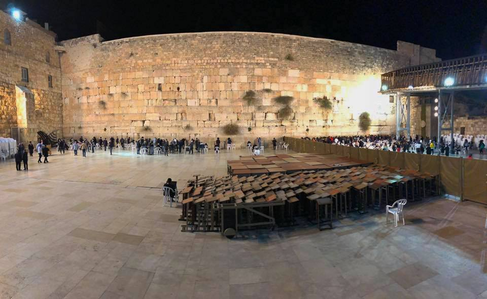 "Visiting the Western Wall at night. The wall is not actually part of the ancient YHWH temple in Jerusalem, but rather is one face of an enormous platform built in the Herodian period. The platform supported porches, open courtyards, walls, and, in the center, the Second Temple. The ""men's side"" of the Western Wall is pictured here. Image by Tess."