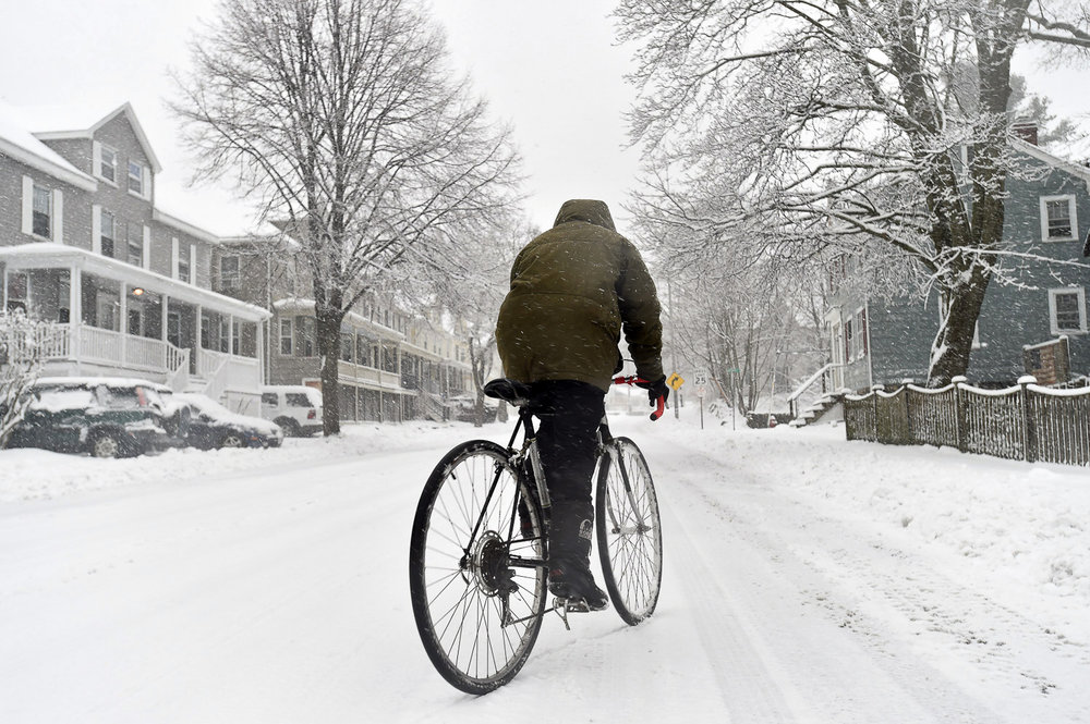 Nikon D4s, 1/250 @ f/5.6, ISO 200, 17-35mm  Beverly resident Libby Burns rides a bicycle along Essex Street during Winter Storm Stella.