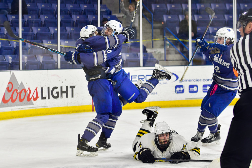 Nikon D4s, 1/800 @ f/2.8, ISO 1,250, 70-200mm Stoneham's Nick Federico, Nick Feliciano, and Adrian Sousa celebrate a goal during their Division 2 North win over North Reading, 2-1, in double overtime at the Tsongas Center at UMass Lowell.