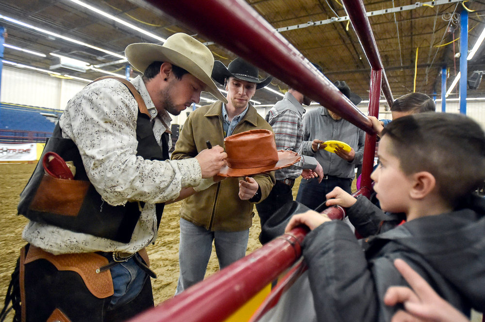 Nikon D4s, 1/1000 @ f/2.8, ISO 8,000, 17-35mm  Daniel Scavone and Ryan O'Donoghue autograph a fans cowboy hat at the conclusion of the Rodeo at The Aleppo Shriners Auditorium in Wilmington, Friday, April 7, 2017. [Wicked Local Staff Photo / David Sokol]