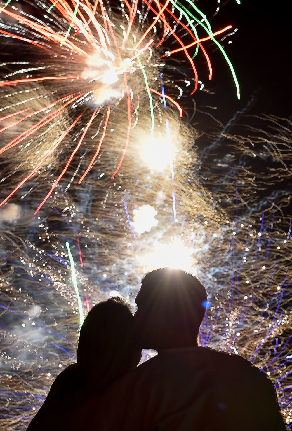 Nikon D4s, .8 sec @ f/9, ISO 100, 24-70mm  A couple shares a kiss as they watch the Independence Day Fireworks display at Trum Field in Somerville, Thursday, June 29, 2017. [Wicked Local Staff Photo / David Sokol]