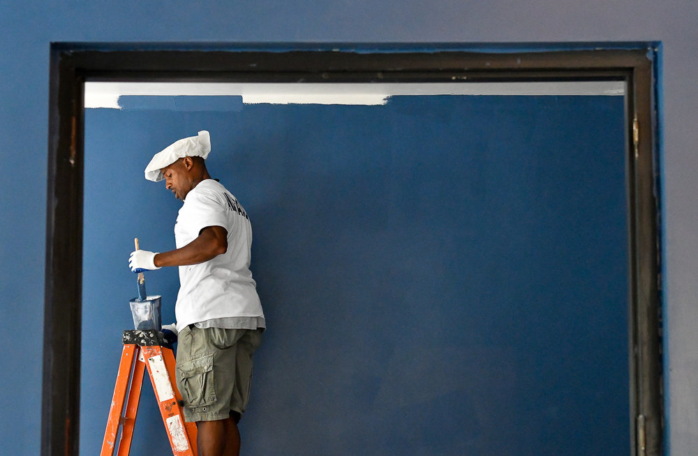 Nikon D500, 1/320 @ f/4.5, ISO 5600, 70-200mm Casey Staton, volunteer from Saugus Lowe's, paints one of the walls inside a new conference space at Medford Vocational Technical High School, Saturday, July 29, 2017. [Wicked Local Staff Photo / David Sokol]