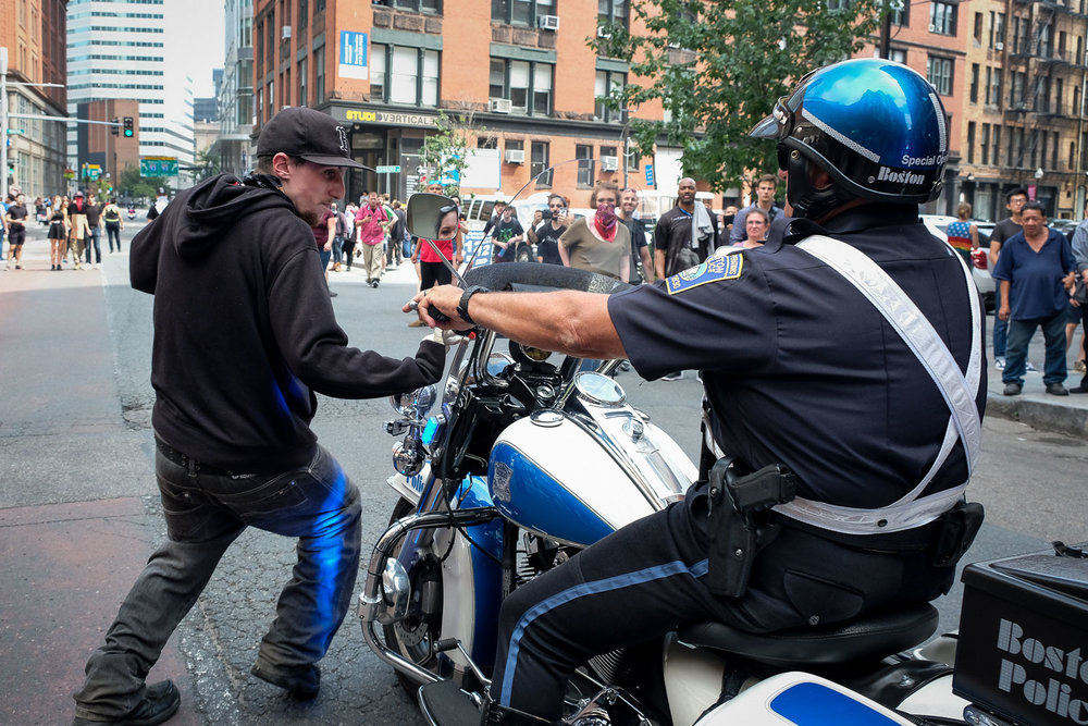 "Fuji X-T2, 1/500 @ f/5, ISO 1250, 18-55mm A counter-protesters moves to avoid a Boston Police officers as they try to secure the scene after the ""Free Speech"" rally on the Boston Common, Saturday, Aug. 19, 2017. [Wicked Local Staff Photo / David Sokol]"