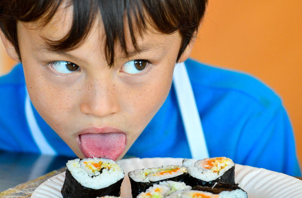 Nikon D500, 1/320 @ f/3.2, ISO 1100, 70-200mm Joey Duffield, 8, uses his tongue to get a taste of sushi he made during a cooking class at Taste Buds Kitchen in Beverly, Wednesday, Oct. 18, 2017.