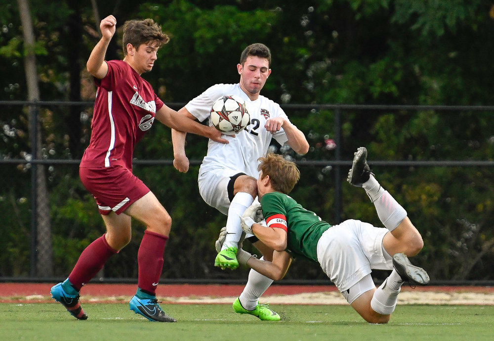 Nikon D500, 1/1250 @ f/4, ISO 2000, 70-200mm with a 1.4x  Dustin Rosh, center, of Reading, accidentally knees his goalkeeper Alex Katsoufis in the face while being pressured for the ball by Will Clifford of Arlington during their game at Reading High School, Thursday, Sept. 14, 2017.