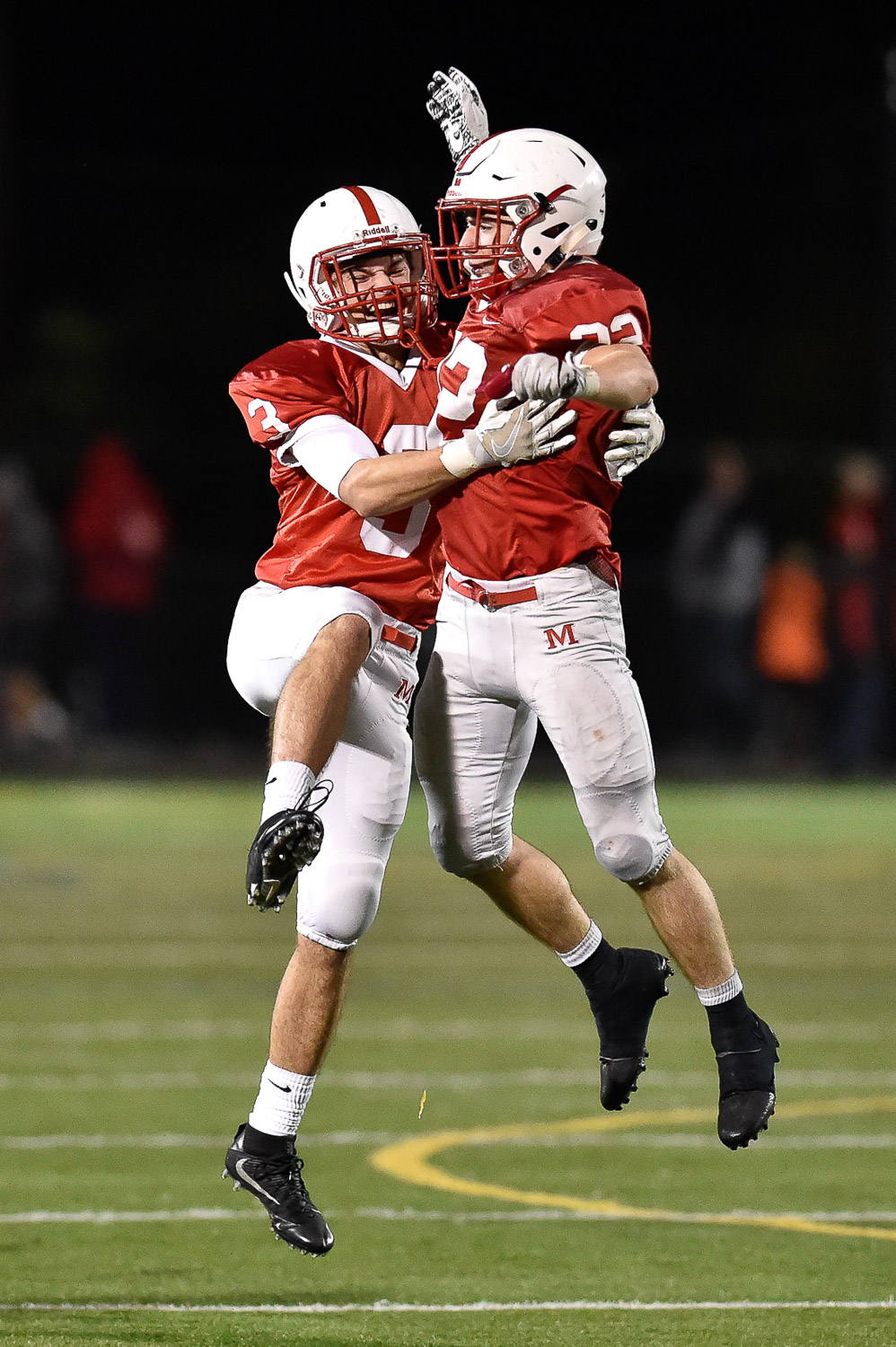Nikon D4s, 1/1250 @ f/2.8, ISO 8000, 300mm Louis Izzi Jr. and Colin Kiernan of Melrose celebrate at the conclusion of their 14-10 win over Dracut at Melrose High School, Friday, Oct. 27, 2017.
