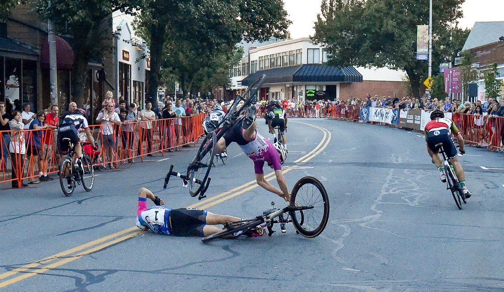 Lucas Fortini is seen flying through the air after making contact Sam Rosenholtz who crashed after crossing the finish line at the conclusion of the Men's State Championship Race during The Gran Prix of Beverly, Wednesday, July 26, 2017. [Wicked Local Staff Photo / David Sokol]