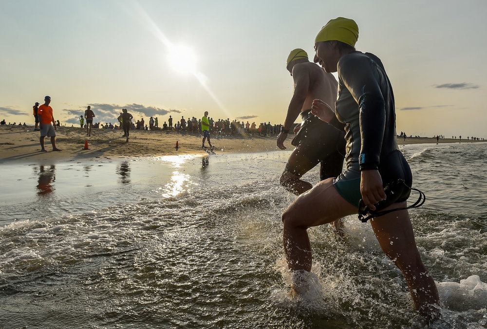 Athletes head out of the Atlantic Ocean after completing a half mile swim during the 16th annual Ipswich YMCA Triathlon at Cranes Beach, Friday, Aug. 25, 2017. [Wicked Local Staff Photo / David Sokol]