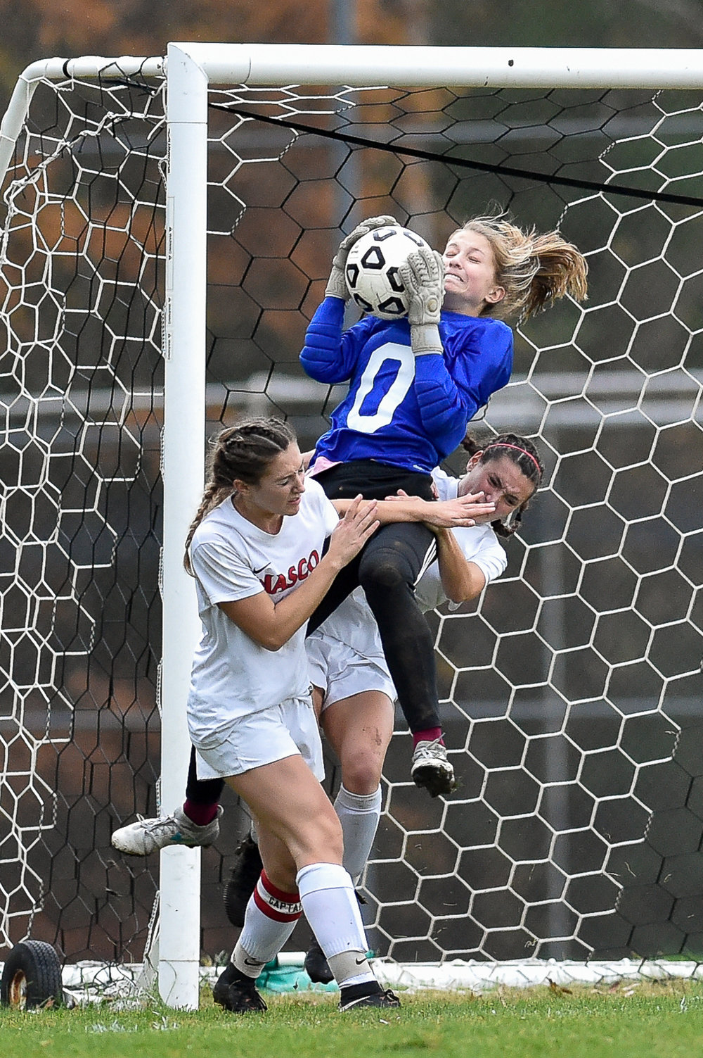 Arlington goal keeper Claire Ewen makes this save as she gets tangled up with Regan Pratt and Olivia Bonacorso of Masconomet during their 2-0 MIAA North Division 2 game win at Masconomet High School, Monday, Nov. 6, 2017. [Wicked Local Staff Photo / David Sokol]
