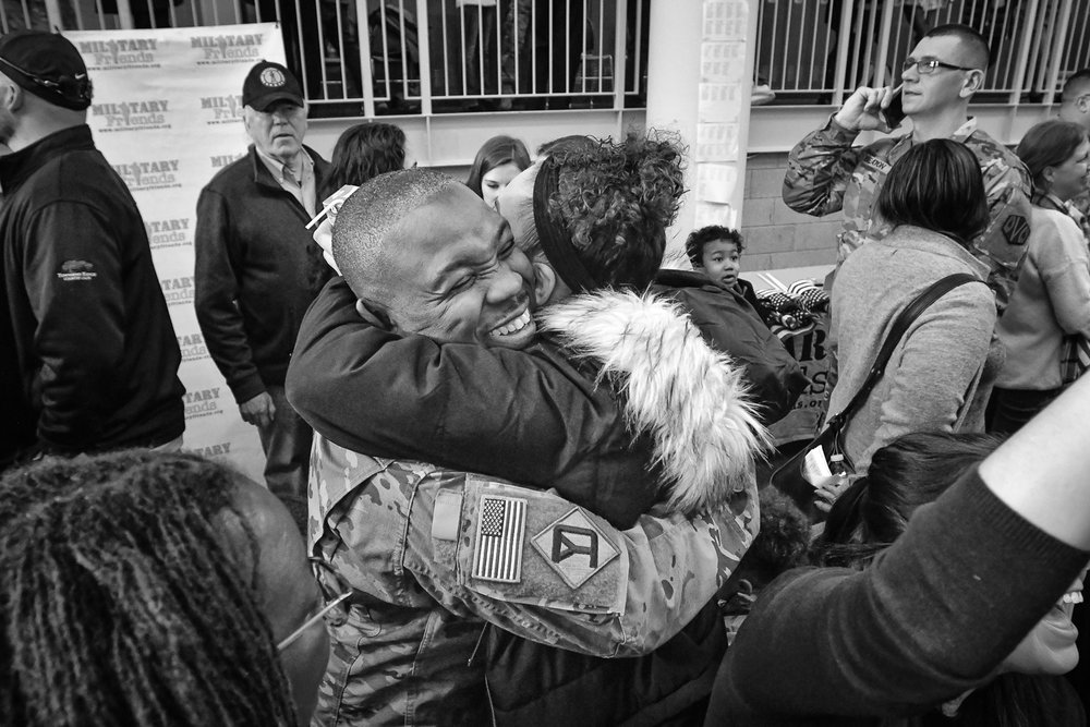 Nikon D4s, 1/250 @ f/4.5, ISO 3200, 17-35mm  Sergeant Briama Massaquoi, of Cambridge, recieves a hug from Shakyla Platt at the conclusion of the 151st Regional Support Group Deployment Ceremony at Reading High School on Sunday, Jan. 21, 2018. Soldiers from the 151st Regional Support Group, Massachusetts Army National Guard will soon be deployed to southwest Asia for nine months. [Wicked Local Staff Photo / David Sokol]