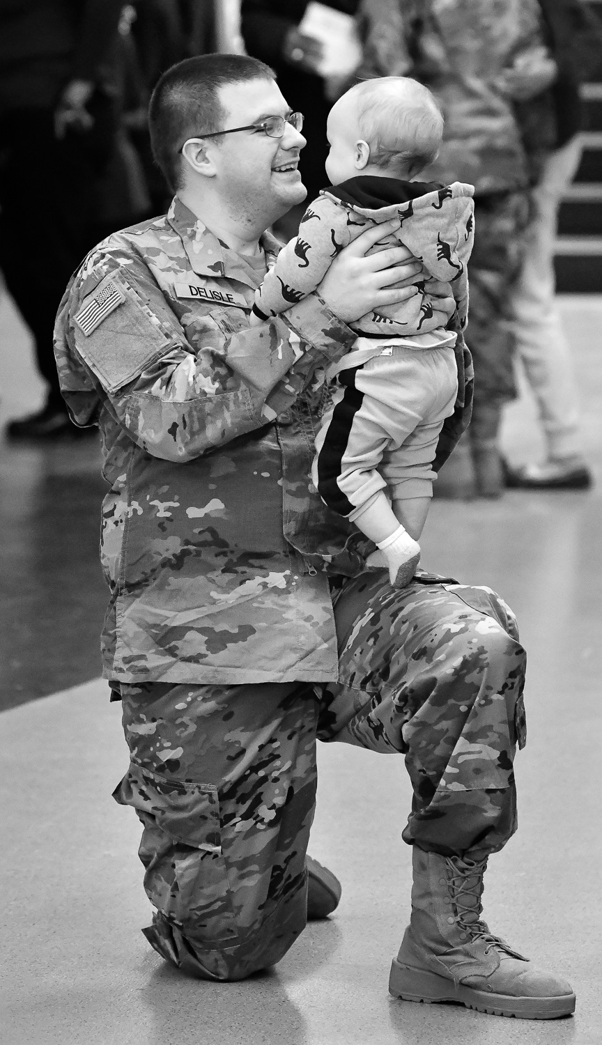 Nikon D500, 1/320 @ f/4, ISO 7200, 70-200mm  Specialist Ben Delisle, of South Bridge, holds his son Theadore, 11 months, at the conclusion of a deployment ceremony at Reading High School on Sunday, Jan. 21, 2018. Soldiers from the 151st Regional Support Group, Massachusetts Army National Guard will soon be deployed to southwest Asia for nine months. [Wicked Local Staff Photo / David Sokol]