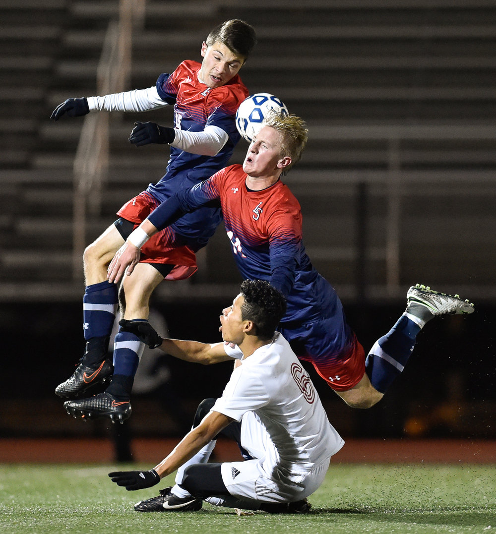 1st Place, Sports Photo  Lincoln-Sudbury's Andre Kotikian and Landon DeCesare-Fousek get tripped up Somerville's Edwin Mejia Sanchez as they battle for a loose ball during their north division 1 game at Manning Field in Lynn on Wednesday, Nov. 9, 2016.
