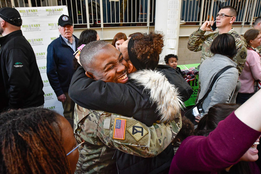 Second Place General News:  Sergeant Briama Massaquoi, of Cambridge, receives a hug from Shakyla Platt at the conclusion of the 151st Regional Support Group Deployment Ceremony at Reading High School on Sunday, Jan. 21, 2018. Soldiers from the 151st Regional Support Group, Massachusetts Army National Guard will soon be deployed to southwest Asia for nine months. [Wicked Local Staff Photo / David Sokol]