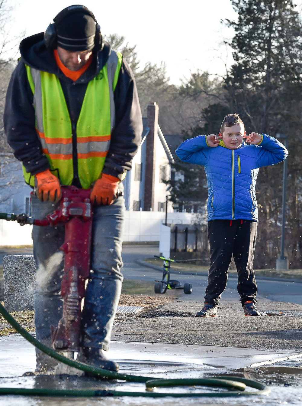 First Place Spot News:  A young boys blocks his ears as an Ipswich Water Department worker uses a jackhammer to break apart the pavement after a water-main break on High Street near Rosewood Drive on Monday, March 5, 2018. [Wicked Local Staff Photo / David Sokol]