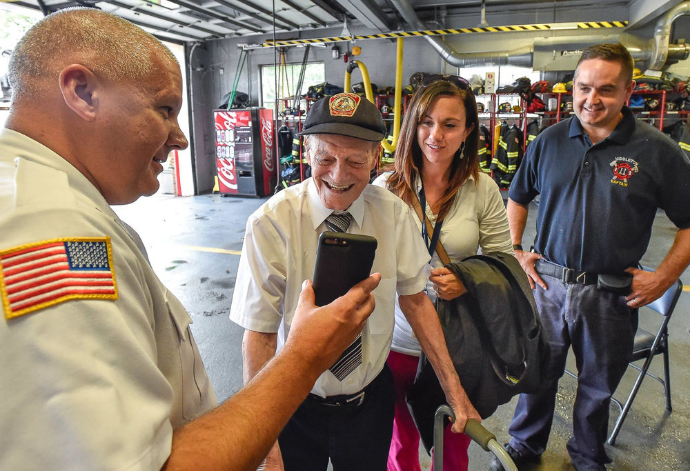 3 of 9 Middleton Fire Chief Thomas Martinuk holds up a cell phone for honorary Middleton firefighter Bobby Jensen as he Face Times with Billy Clough an old neighbor and part time Middleton firefighter while Maureen Brancato, Hospice Nurse at Compassus, and firefighter David Thibeault look over his shoulder during his visit at the Middleton Fire Department, Thursday, Sept. 14, 2017. [Wicked Local Photo / David Sokol]