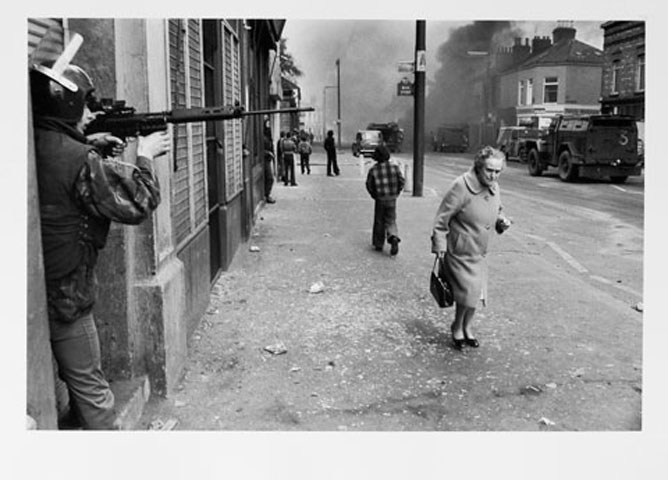 NORTHERN IRELAND. Belfast. Catholic West Belfast. Falls Road. Hijacked vehicle burns in the background marking the anniversary of the British Policy of internment without trial. 1978.