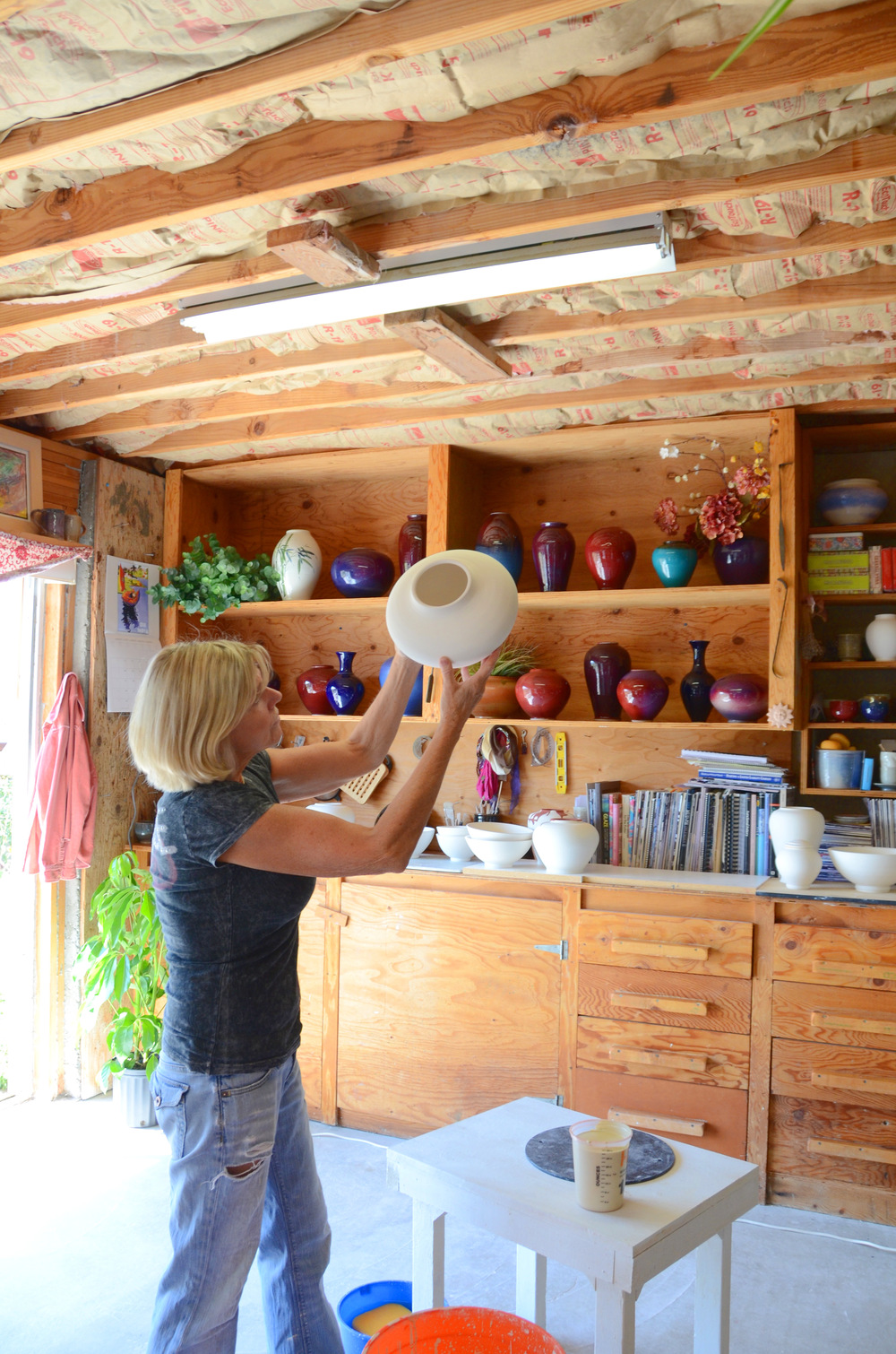 Shelly Caldwell inspecting a new porcelain piece in their Park City studio | Caldwell Pottery