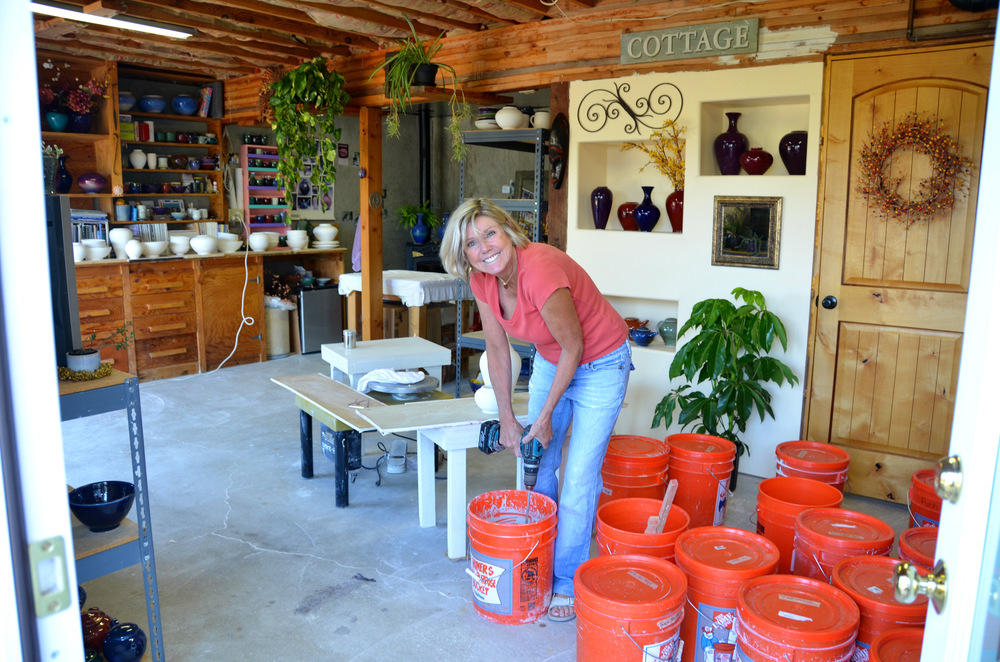 Shelly Caldwell hand glazing their porcelain pieces in their Park City studio | Caldwell Pottery