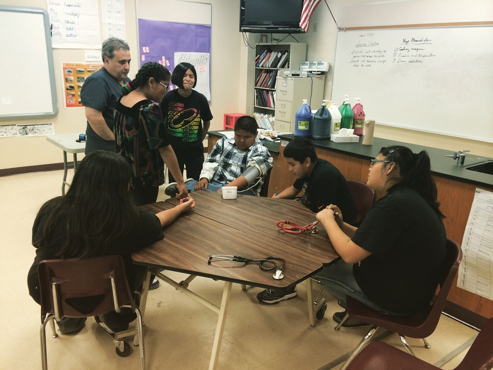 Nurse Alex Ortega teaches students how to measure blood pressure
