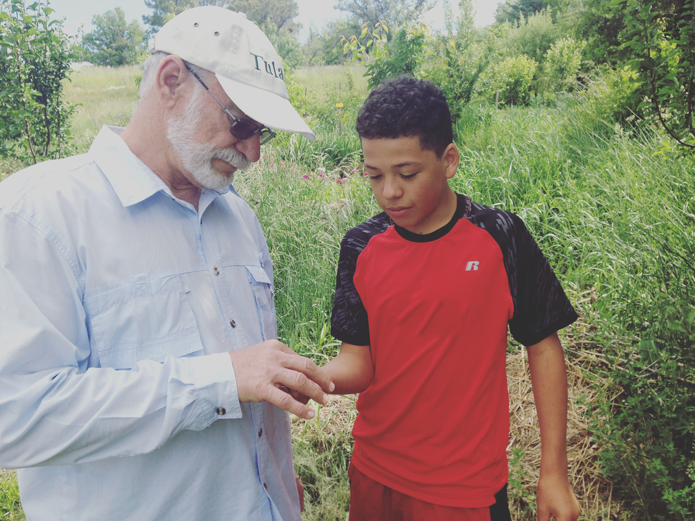 Mr Hoodless helps a student identify a macroinvertebrate