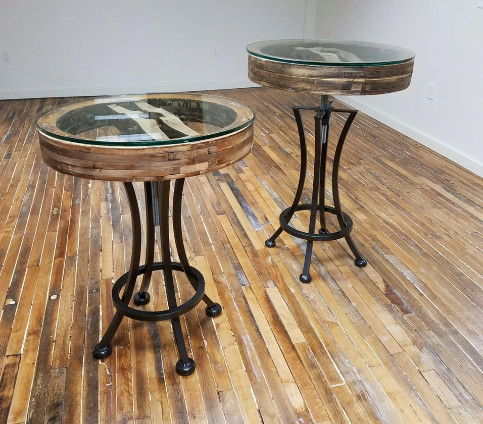 Fly Wheel High Top Tables - Once fly wheels for a grist mill now tops for our adjustable hi-top tables. Perfect as a home bar table or small eat-in kitchen, these tables feature very sturdy legs, thick glass for durability and a locking nut to secure the top at just the right height.