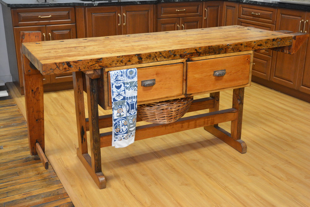 Work Bench Island - This former work bench is a statement-making addition to a kitchen. The bench is a perfect island height and features tool notches that are convenient for kitchen utensils as you're whipping up a favorite dish. The double-sided drawers offer plenty of storage, and the bottom rails create a handy shelf for baskets, platters and more.