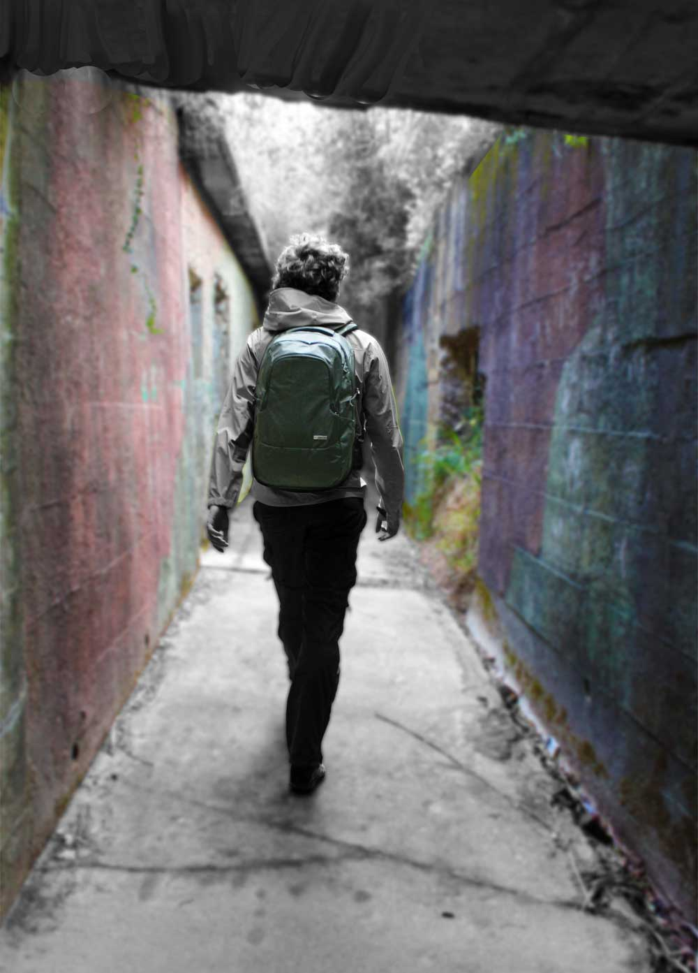 Young-man-walking-down-alley-with-pacsafe-backpac