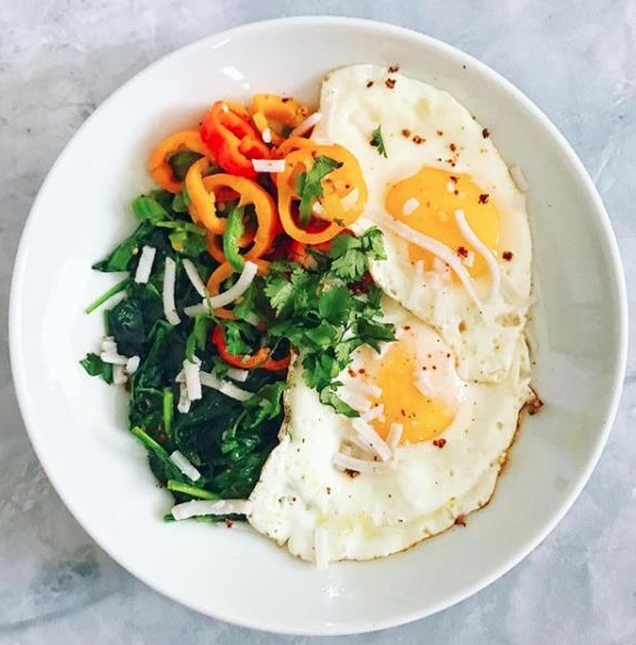 Quick Mexican-Inspired Breakfast: Spinach sautéed in garlic and ghee with sautéed sweet bell peppers and chopped jalapeño with two pasture-raised runny eggs, vegan mozzarella, chili lime seasoning, and cilantro
